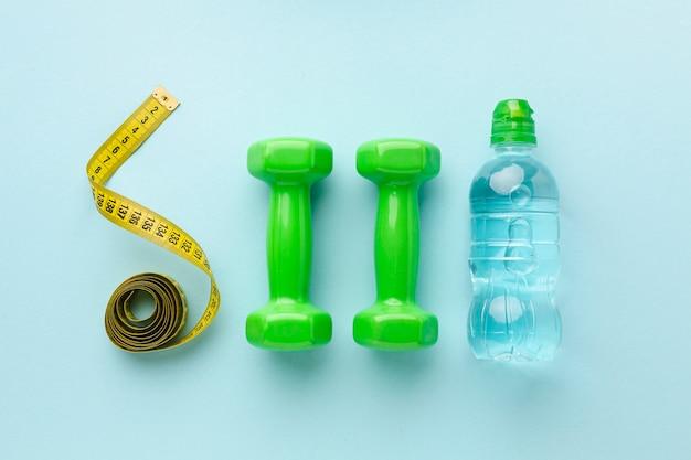Bovenaanzicht gewichten meter en fles water Gratis Foto