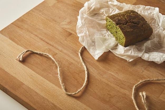 Bovenaanzicht gezonde voeding spinazie brood geïsoleerd op een houten bord op tafel in ambachtelijk papier Gratis Foto