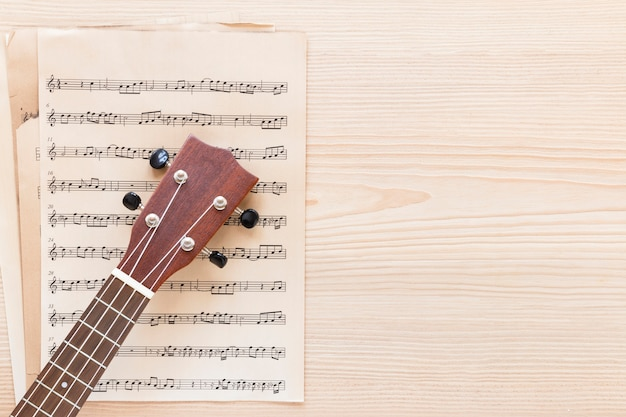 Bovenaanzicht gitaar hals met muziek blad Gratis Foto