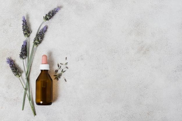 Bovenaanzicht glazen fles en lavendel kopie ruimte Gratis Foto