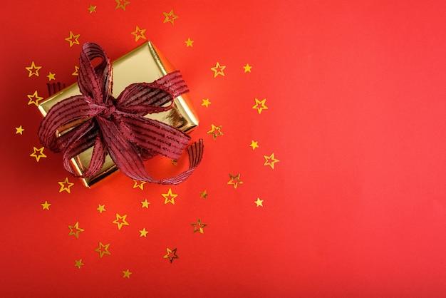 Bovenaanzicht gouden geschenkdoos met bourgondische boog en verstrooiing van gouden confetti sterren op rode achtergrond Premium Foto