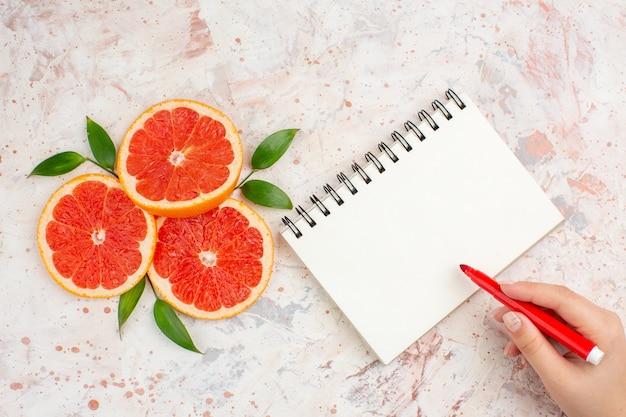 Bovenaanzicht grapefruits plakjes met bladeren een kladblok rode marker in vrouwelijke hand op naakt oppervlak Gratis Foto