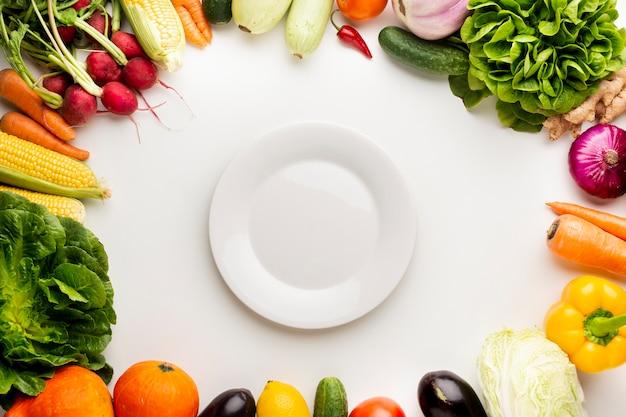 Bovenaanzicht groenten frame met lege plaat Gratis Foto