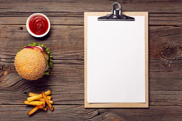 Bovenaanzicht hamburger met mock-up klembord Gratis Foto