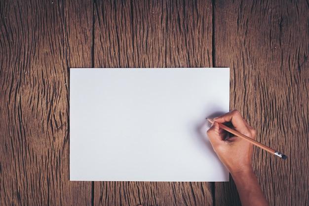 Bovenaanzicht hand met blanco witboek Gratis Foto