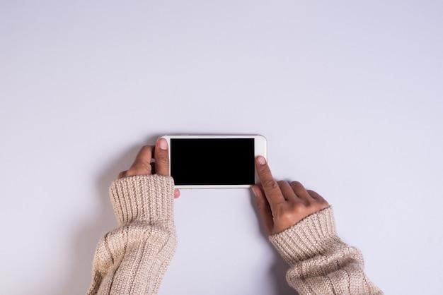 Bovenaanzicht hand met mobiele telefoon op witte achtergrond Gratis Foto