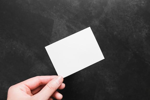 Bovenaanzicht hand met papieren visitekaartje Premium Foto
