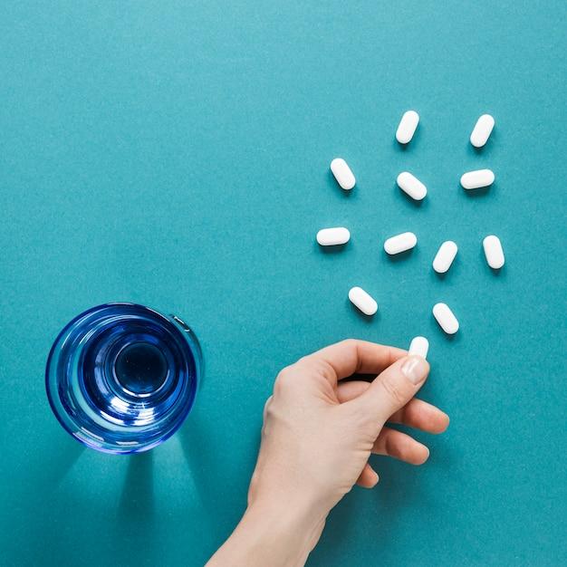 Bovenaanzicht hand met pijnstillers op de tafel Gratis Foto