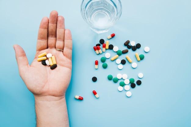 Bovenaanzicht hand met pillen Gratis Foto