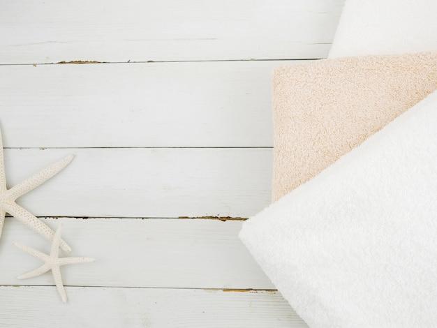 Bovenaanzicht handdoeken en zeesterren Gratis Foto