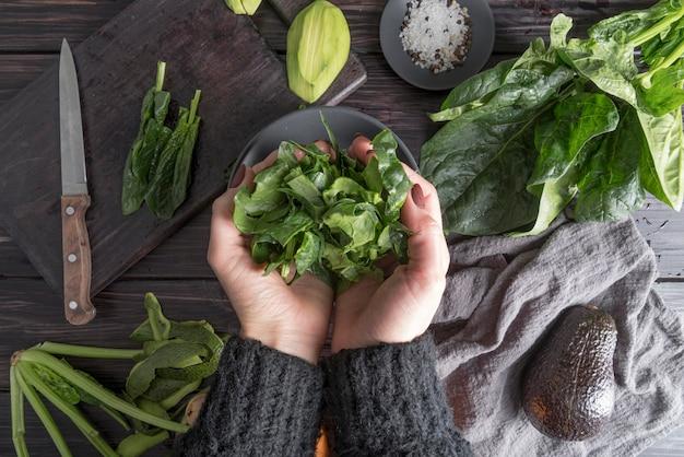 Bovenaanzicht handen met biologische salade Gratis Foto