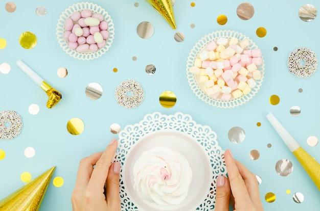 Bovenaanzicht handen met een bord met muffin Gratis Foto