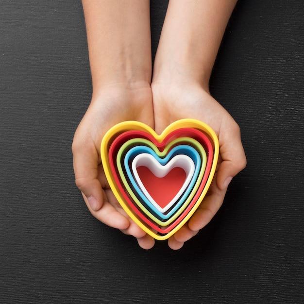 Bovenaanzicht handen met elementen in de vorm van harten Gratis Foto