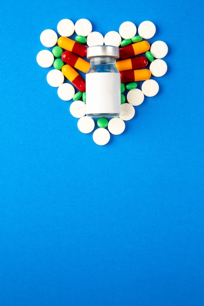 Bovenaanzicht hartvormige pillen verschillend gekleurd met vaccin op blauwe achtergrond Gratis Foto
