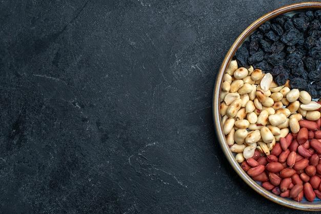 Bovenaanzicht hazelnoten en rozijnen en andere noten op donkergrijze tafelnoot snack droog fruit foto Gratis Foto