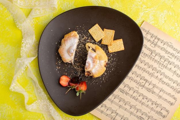 Bovenaanzicht heerlijk gebak binnen plaat met crackers op gele tafel, bak zoete thee gebak Gratis Foto