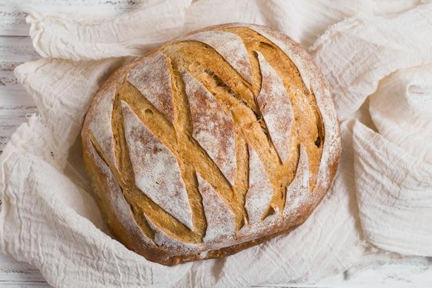Bovenaanzicht heerlijk gebakken brood op witte doek Gratis Foto