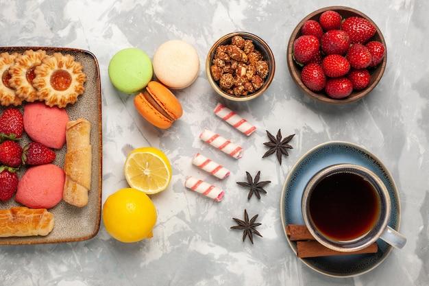 Bovenaanzicht heerlijke bagels met taarten, thee, verse aardbeien en koekjes op het witte bureau Gratis Foto