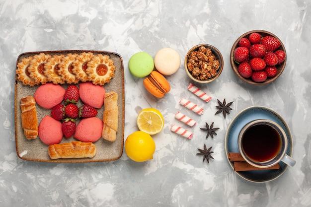 Bovenaanzicht heerlijke bagels met taarten thee verse aardbeien thee en koekjes op wit bureau Gratis Foto