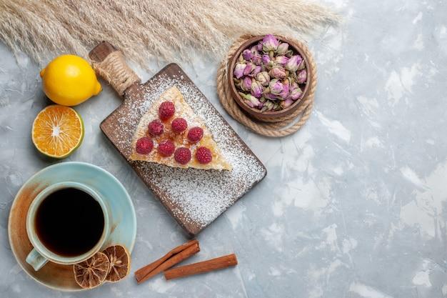 Bovenaanzicht heerlijke cakeplak met kopje thee en citroenen op het licht bureau cake koekje zoete suiker bakken Gratis Foto