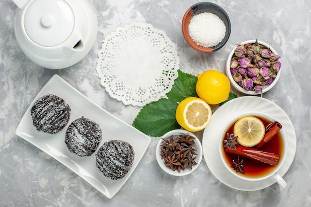 Bovenaanzicht heerlijke chocoladetaarten kleine ronde gevormd met citroen op wit bureau fruit cake koekje zoete suiker bak cookie Gratis Foto