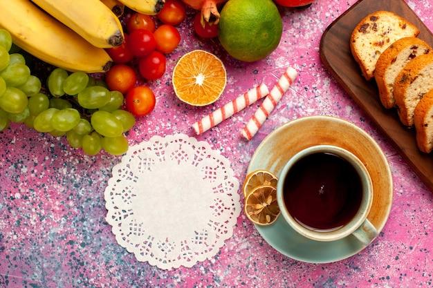 Bovenaanzicht heerlijke fruitsamenstelling met gesneden cakes en kopje thee op lichtroze bureau Gratis Foto