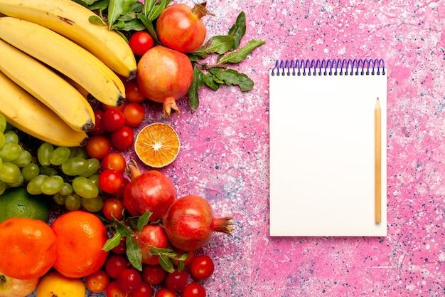Bovenaanzicht heerlijke fruitsamenstelling op lichtroze bureau Gratis Foto