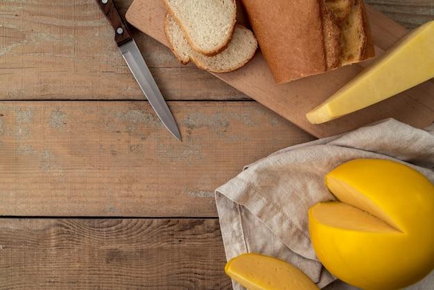 Bovenaanzicht heerlijke kaas met brood en een mes Gratis Foto