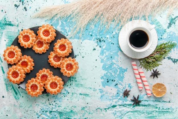 Bovenaanzicht heerlijke kleine koekjes met kopje koffie op blauwe bureau cookie biscuit zoete suiker kleur thee Gratis Foto