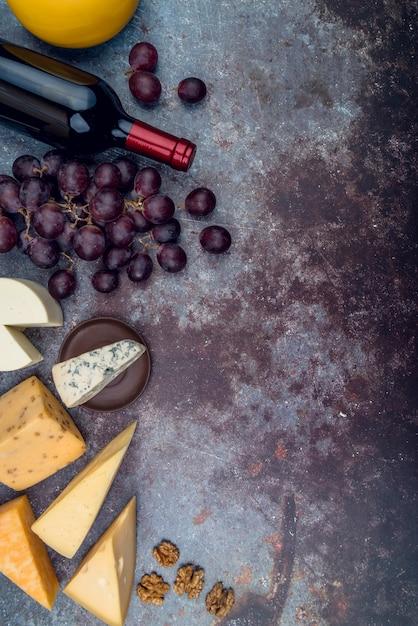 Bovenaanzicht heerlijke selectie van kaas met wijn en druiven Gratis Foto