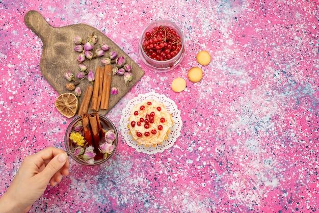 Bovenaanzicht heerlijke slagroomtaart met verse rode veenbessen samen met kaneel en thee op het paarse bureau Gratis Foto