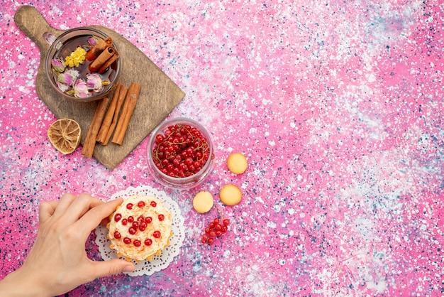 Bovenaanzicht heerlijke slagroomtaart met verse rode veenbessen samen met kaneel en thee op het paarse suikergoed Gratis Foto
