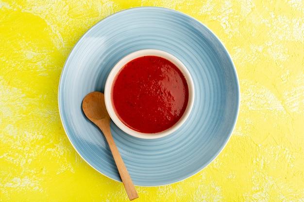 Bovenaanzicht heerlijke tomatensoep in blauwe plaat op gele tafel, soep eten maaltijd diner Gratis Foto