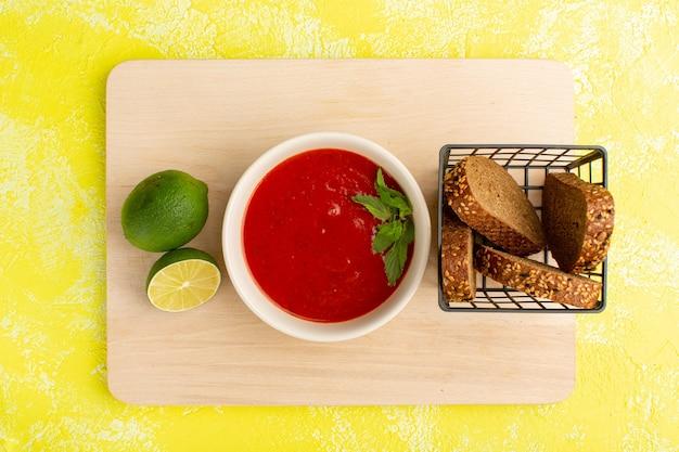 Bovenaanzicht heerlijke tomatensoep met broodbroodjes citroenplak op gele tafel, soep maaltijd diner groente Gratis Foto