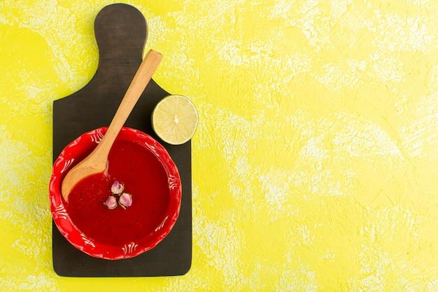 Bovenaanzicht heerlijke tomatensoep met citroen op gele tafel, soep maaltijd plantaardig voedsel Gratis Foto