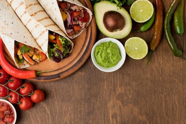 Bovenaanzicht heerlijke tortilla's met guacamole op tafel Gratis Foto