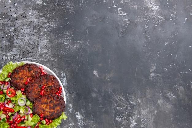 Bovenaanzicht heerlijke vleeskoteletten met frisse salade Gratis Foto