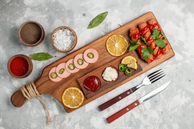 Bovenaanzicht heerlijke worstjes met citroen en kruiden op licht-wit bureau maaltijd fruit groente eten Gratis Foto