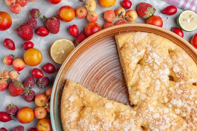 Bovenaanzicht heerlijke zoete taart gebakken met fruit op licht bureau fruit vers zacht bak zoet koekje Gratis Foto