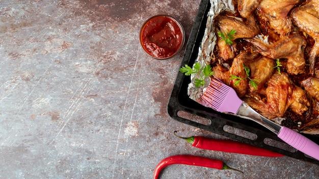 Bovenaanzicht hete kippenvleugels in bakplaat Gratis Foto