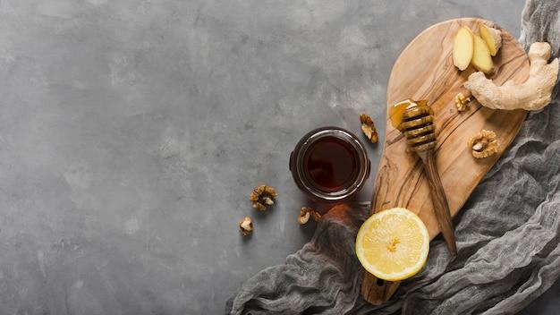 Bovenaanzicht honingpot met voedsel en honinglepel Gratis Foto