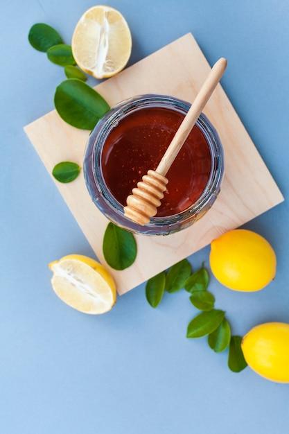 Bovenaanzicht honingpot op de tafel met citroenen Gratis Foto