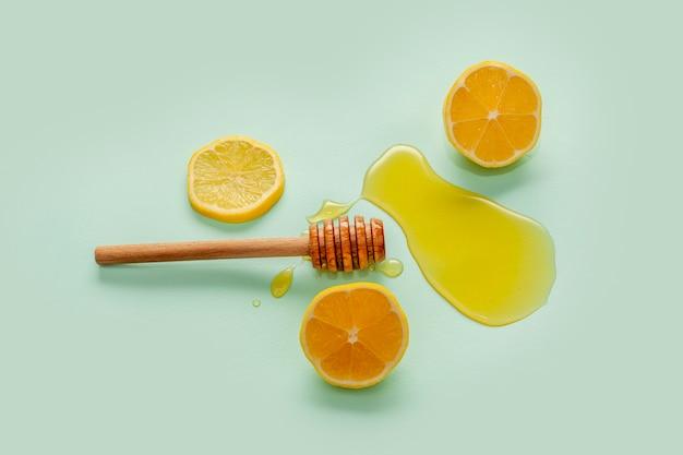 Bovenaanzicht honingstok en schijfjes citroen Gratis Foto