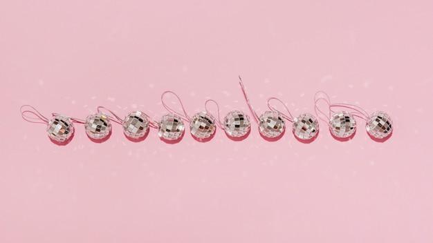 Bovenaanzicht horizontale lijn van kerstballen op roze achtergrond Gratis Foto
