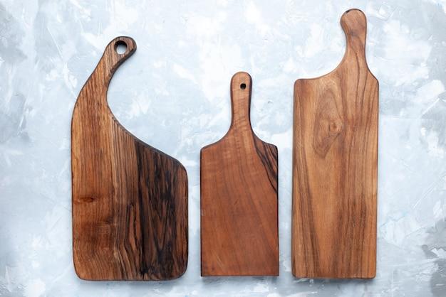 Bovenaanzicht houten bureau anders gevormd gemaakt van hout voor voedsel op de lichte houten fotokleur als achtergrond Gratis Foto