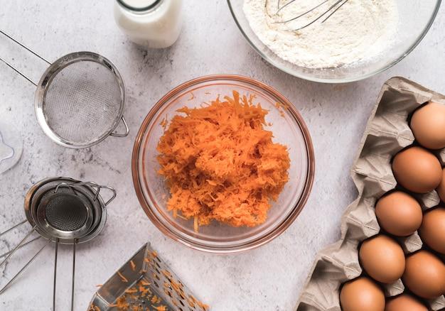 Bovenaanzicht in blokjes gesneden wortelen in een kom omringd door eieren Gratis Foto