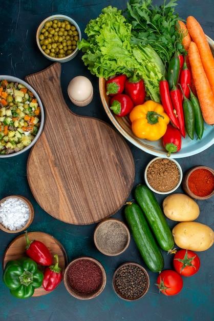 Bovenaanzicht in de verte gesneden groentesalade gepeperd met plakjes kip binnen plaat met verse groenten op blauw bureau snack lunch salade plantaardig voedsel Gratis Foto