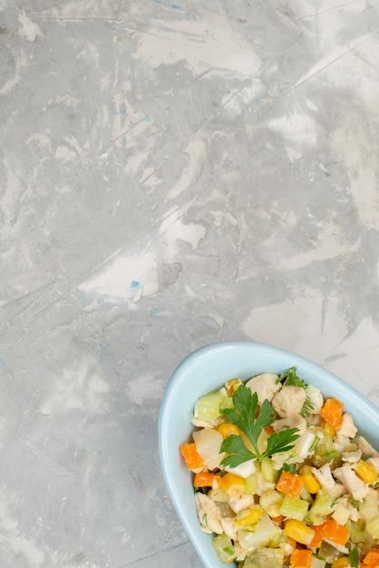 Bovenaanzicht in de verte gesneden groentesalade in blauwe plaat op de lichte maaltijd van de achtergrond de plantaardige voedselsalade Gratis Foto