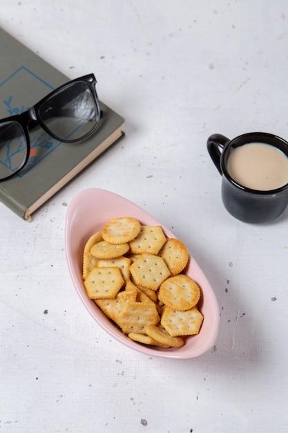 Bovenaanzicht in de verte roze plaat met crackers en chips samen met zonnebril en kopje melk op de lichte achtergrond knapperige cracker foto snack Gratis Foto