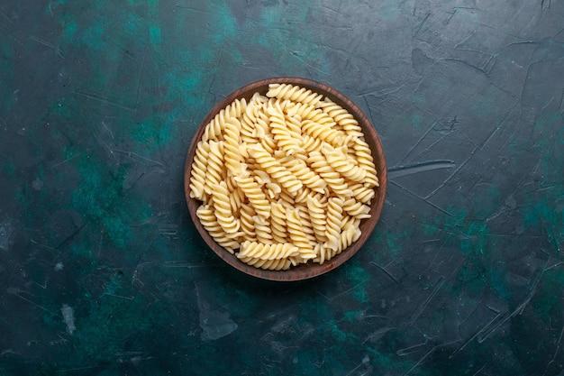 Bovenaanzicht italiaanse pasta heerlijk kijken in bruine pot op donkerblauw bureau italiaanse pasta eten maaltijd diner koken keuken deeg Gratis Foto